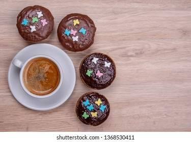 chocolate muffins with cup of coffee on wooden ground