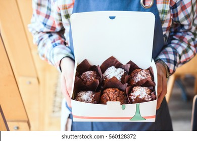 Chocolate muffins in hands server at the coffee shop.