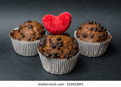 chocolate muffins with heart  on a dark background