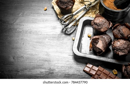 Chocolate muffins with ingredients. On the black chalkboard.