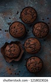 chocolate muffins on  dark blue background, top view