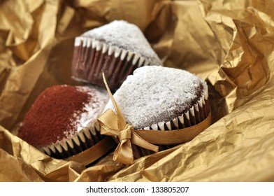 Chocolate muffins packed in golden paper