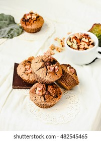 chocolate muffins with pieces of dark chocolate and walnut, light comfortable background