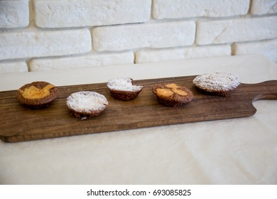 Chocolate muffins or sponge cakes on wooden table