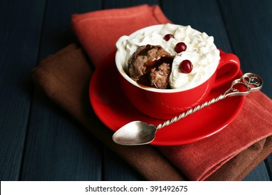 Chocolate mug cake with cream and cranberry on a table in front of dark background