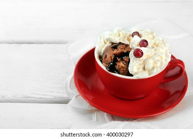 Chocolate mug cake with cream and cranberry on a white napkin