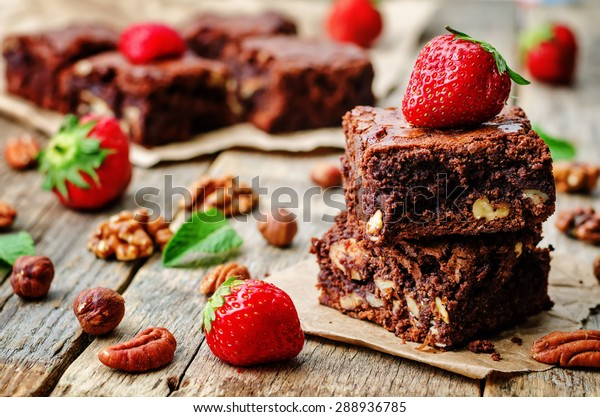 chocolate nut brownie cake decorated with strawberries. the toning. selective focus