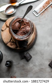 Chocolate nut spread in a glass jar on a dark table with vintage cutlery. Dark photo. Homemade sweets.
