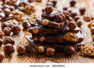 Chocolate and nuts: hazelnuts and walnuts on a wooden background, selective focus