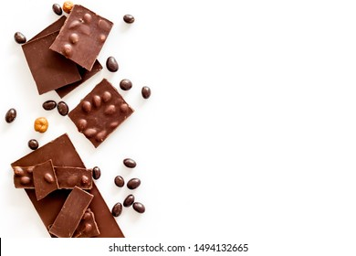 Chocolate with nuts and its ingredients on white background top view copyspace