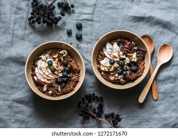 Chocolate oatmeal with apples and blueberries - healthy vegetarian breakfast on a grey background, top view. Flat lay, copy space