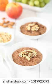 Chocolate oatmeal or oat porridge with toasted almond slices and grated chocolate on top, fresh fruits in the back, photographed with natural light (Selective Focus in the middle of the first bowl)