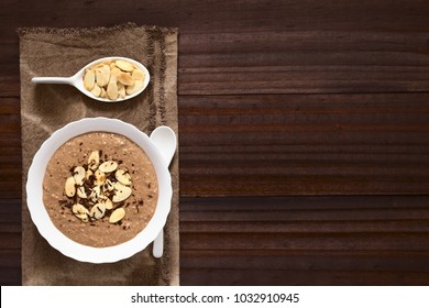 Chocolate oatmeal or oat porridge with toasted almond slices and grated chocolate on top served in small bowl, photographed overhead with natural light (Selective Focus, Focus on the porridge)