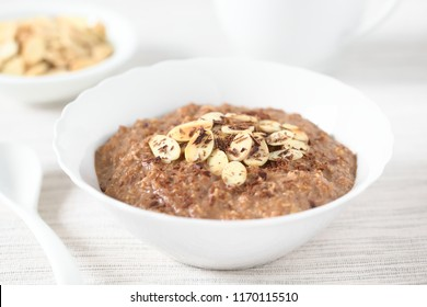 Chocolate oatmeal or oat porridge with toasted almond slices and grated chocolate on top served in small bowl, photographed with natural light (Selective Focus, Focus in the middle of the porridge)