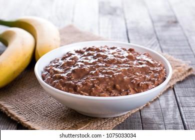 Chocolate oatmeal in white bowl for breakfast, horizontal