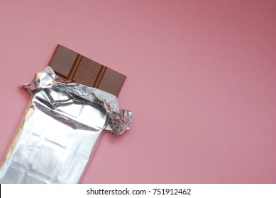 Chocolate on a Foil on a Pink Background in the Corner