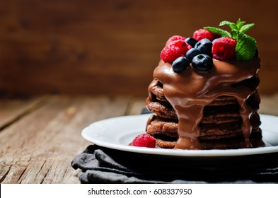 chocolate pancake with blueberries, raspberries and chocolate sauce. the toning. selective focus