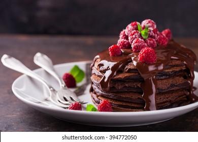 Chocolate pancake with chocolate glaze,raspberries and mint.selective focus