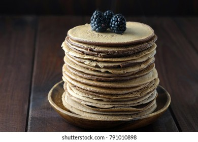 Chocolate pancakes with blackberries on wooden plate on dark-brown background. Traditional food for Russian holiday Maslenitsa.