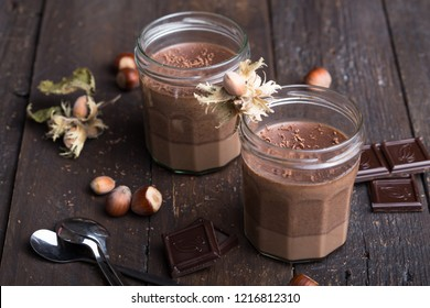 Chocolate Panna cotta in two glasses is an Italian dessert of sweetened cream thickened with gelatin and molded.
