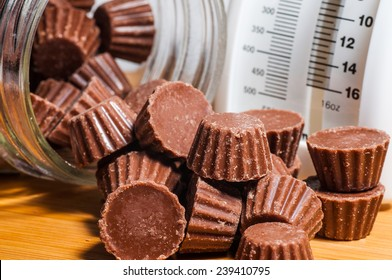Chocolate peanut butter cups spilling out of a clear jar on a wood background.