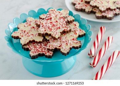 Chocolate peppermint bark in snowflake shape on bright blue metal plate with red and white striped peppermint sticks