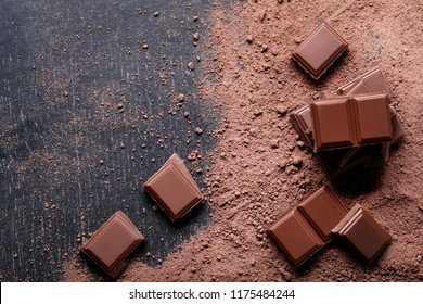 Chocolate pieces with cocoa powder on wooden table