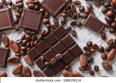 Chocolate pieces with coffee beans on light textured background