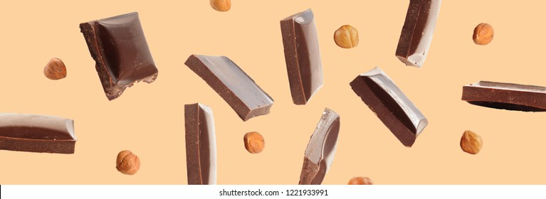 Chocolate pieces and hazelnuts falling over beige background. Sweet food concept