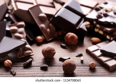 Chocolate pieces with nuts on brown wooden table