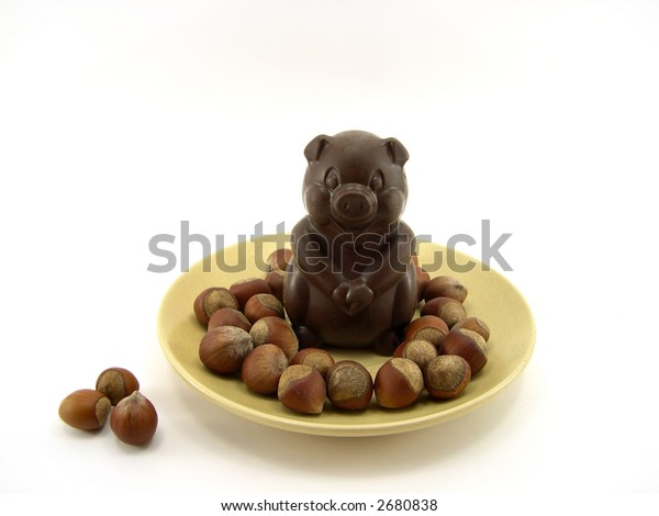 Chocolate a pig in a plate and nuts on a white background