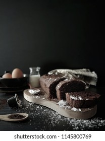 Chocolate Pound Cake with Ingredients, shot against Black background. Dark food photography for chocolate cake on a wooden chopping board.