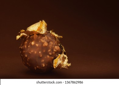 Chocolate praline with edible gold on brown dark background low key