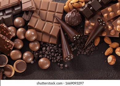 Chocolate pralines and chocolate bar pieces / Assortment of fine chocolates in white, dark, and milk chocolate.