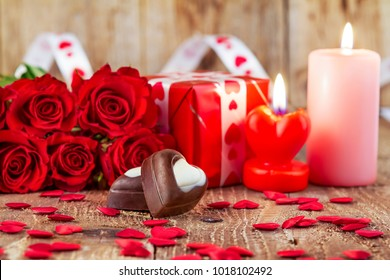 Chocolate pralines in front of bouquet of red roses and candles on wooden background. Valentines day concept. Mothers day concept. Focus on pralines.