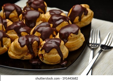 Chocolate profiterole with cream on wooden table