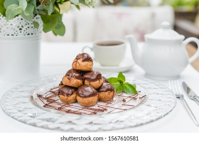 Chocolate profiteroles on a white plate with tea