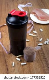 Chocolate protein shake, shaker and round scoop
