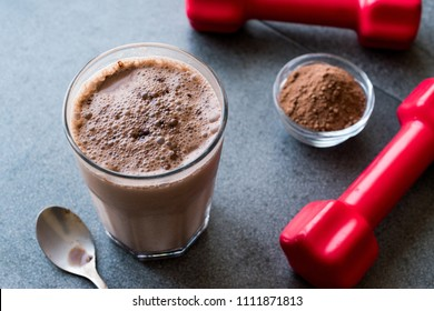 Chocolate Protein Shake Smoothie with Whey Protein Powder and Red Dumbbells. Sports Drink