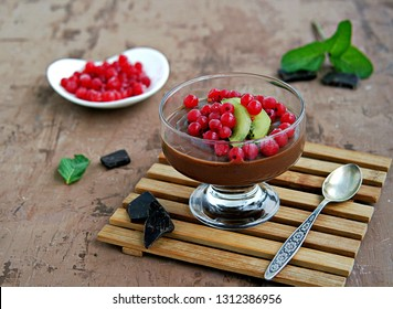 Chocolate pudding with red currants and kiwi in a glass ice-cream bowl on a brown concrete background.