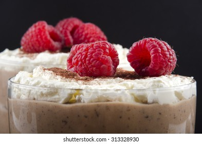 chocolate pudding with whipped cream and raspberry in a glass