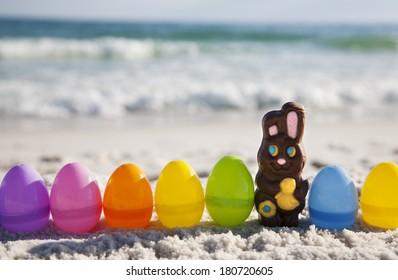 Chocolate Rabbit and easter eggs on ocean beach