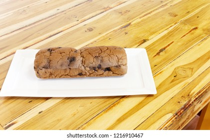 Chocolate and Raisin bread on a white plate, on a wooden table for afternoon coffee