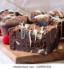 chocolate and raspberry brownies on wooden board with white chocolate drizzle and fresh raspberries