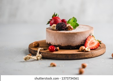 Chocolate raw cake with jam filling with nuts, strawberries and blackberries on a light background side view. Healthy dessert for a healthy diet, without sugar, without flour and eggs.