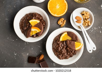Chocolate rice pudding porridge risotto with oranges in chocolate for breakfast. Top view.
