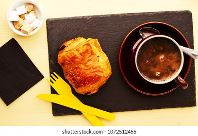 Chocolate Roll and coffee served on black slate