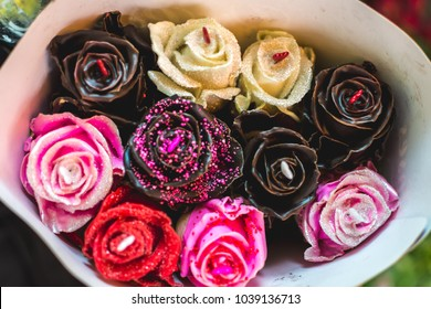Chocolate roses background. Red, brown, yellow and pink chocolate roses.