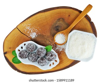 Chocolate rum balls and dessicated coconut powder in porcelain dish over wooden board, isolated on white, top view.