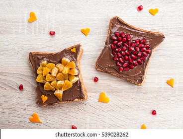 Chocolate sandwich with pomegranate heart and tangerine heart - creative idea for healthy kids breakfast, dessert or holiday meal for Valentines day, top view flat lay